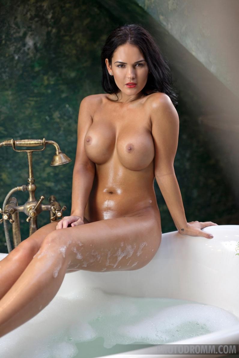 В теплой ванне красивая черноволосая модель обливает из душа заводные дойки