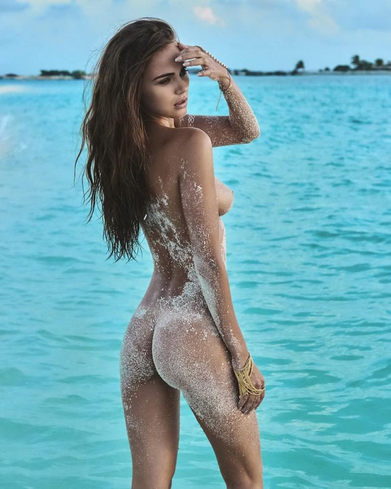Загорелая и худая модель с красивыми лицом и маленькой грудью испачкалась на пляже в мокром песке